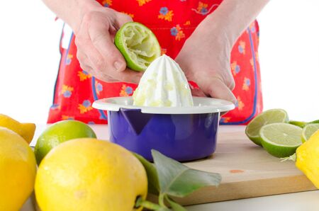 squeezer: Woman squeezing half a lime on a squeezer