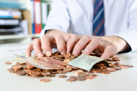Businessman putting his hands on money Stock Photo