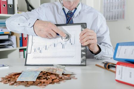 financial market: Businessman analyzing financial market with a stethoscope