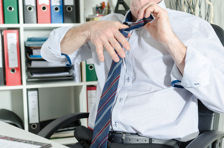 Businessman undoing his tie at office