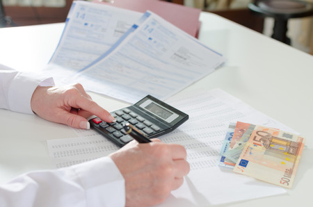 calculating: Woman accountant calculating taxes