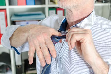 undoing: Businessman undoing his tie at office