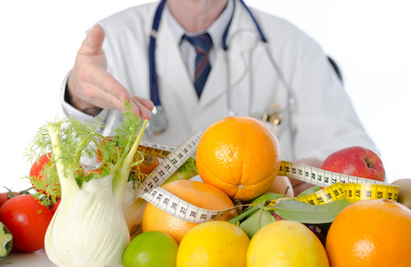 Doctor nutritionist in office showing healthy fruits and vegetables