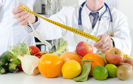 dietetics: Doctor nutritionist in office holding a measure tape