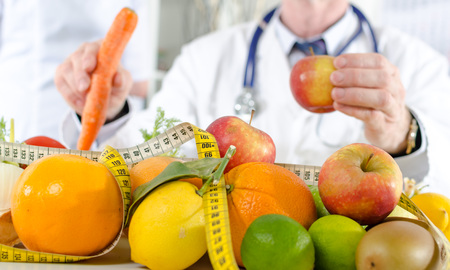 dietetics: Doctor nutritionist in office with healthy fruits