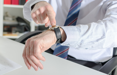 looking at watch: Businessman pointing his watch with his finger at office