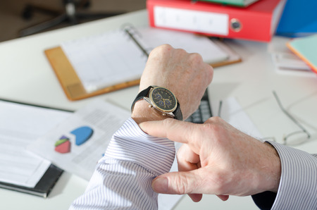 Businessman looking at his watch at office