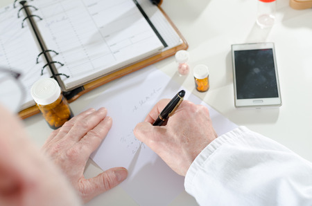 doctor writing: Doctor writing prescription at medical office