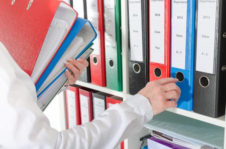 Businesswoman taking binders from a shelf at office Standard-Bild