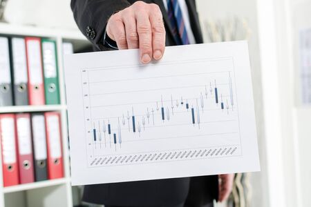 candlestick: Businessman showing candlestick chart at office