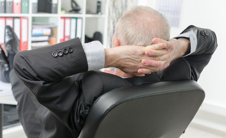 hands behind head: Relaxed businessman during a break at office