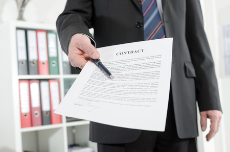 submitting: Businessman standing in his office submitting a contract Stock Photo