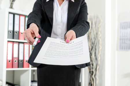 submitting: Businesswoman standing in her office submitting a contract