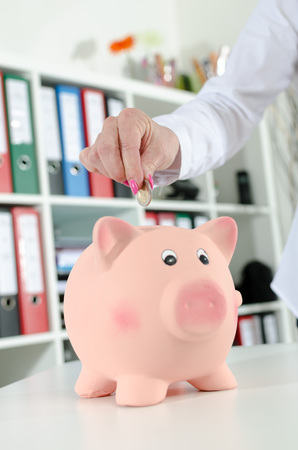 putting: Woman putting a coin into piggy bank Stock Photo