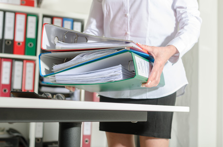 binders: Businesswoman holding binders at office Stock Photo