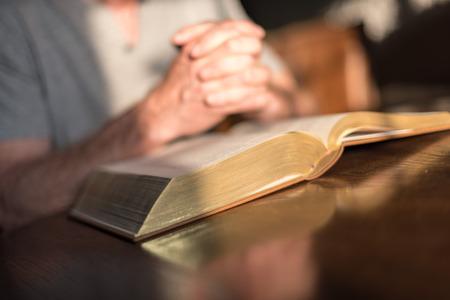 dim light: Man praying hands on a Bible in dim light