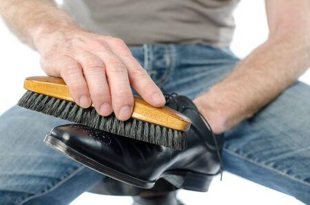 footware: Shoe shiner polishing a black shoe with a brush Stock Photo