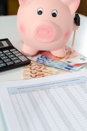 amortization: Piggy bank, banknotes, calculator and amortization schedule
