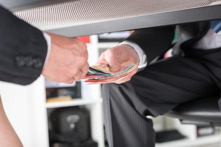 テーブルの下のお金を与える実業家