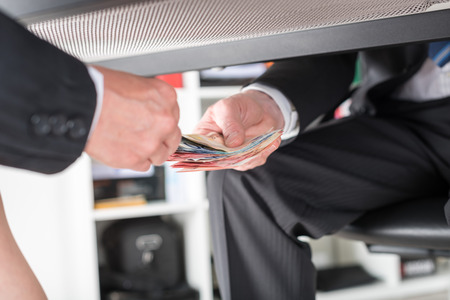 Businessman giving money under a table Stock Photo