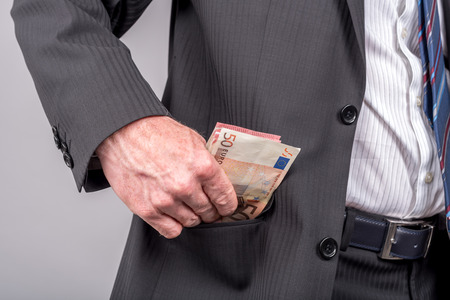 removing: Businessman removing euro banknotes from his pocket