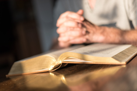 religious text: Man praying hands on a Bible in dim light