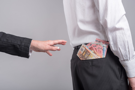 grabbing at the back: Woman about to take money out of back pocket of a businessman Stock Photo