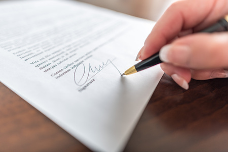 Woman hand signing a contract Banque d'images