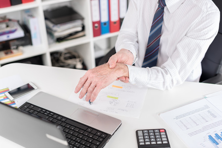 Businessman suffering from wrist pain at office Stok Fotoğraf