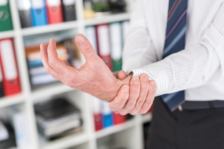 carpal tunnel syndrome: Businessman suffering from wrist pain at office Stock Photo