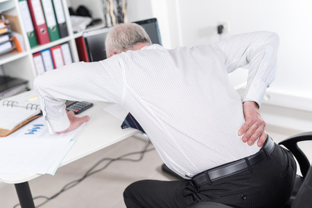 Businessman suffering from back pain at office