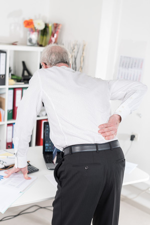 back pain: Businessman suffering from back pain at office