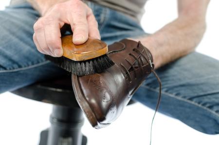 footware: Shoe shiner polishing a brown shoe with a brush
