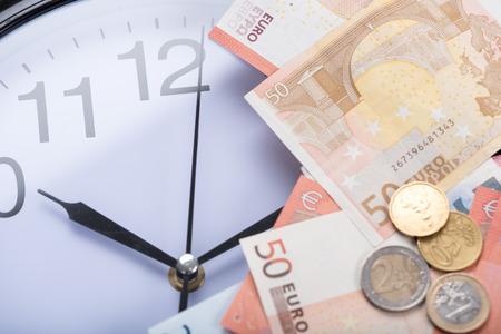 banconote euro: Le banconote in euro su un orologio Archivio Fotografico