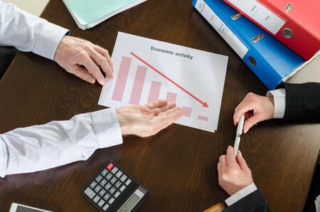 bad economy: Businessman showing graph falling down Stock Photo