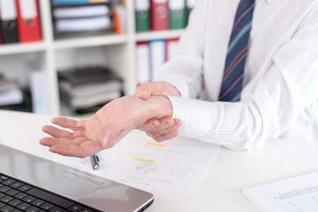 wrist pain: Businessman suffering from wrist pain at office Stock Photo