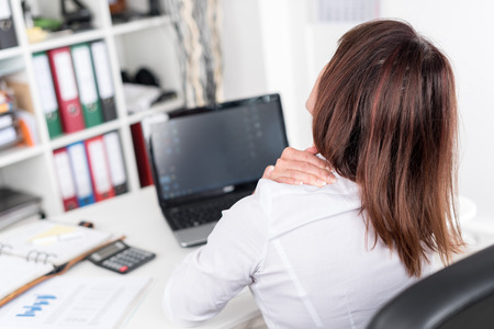 work injury: Businesswoman suffering from neck pain at office