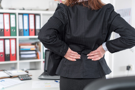 back pain: Businesswoman suffering from back pain at office