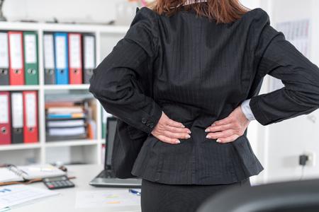 Zakenvrouw lijden aan pijn in de rug op het kantoor van