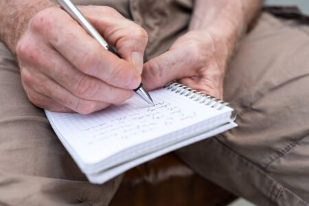pocket book: Man taking notes on a pocket book, closeup