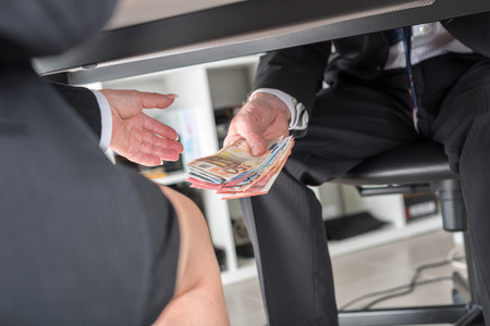 giving money: Businessman giving money under a table Stock Photo
