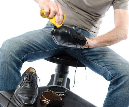 footware: Shoe shiner shining a black shoe with a yellow rag