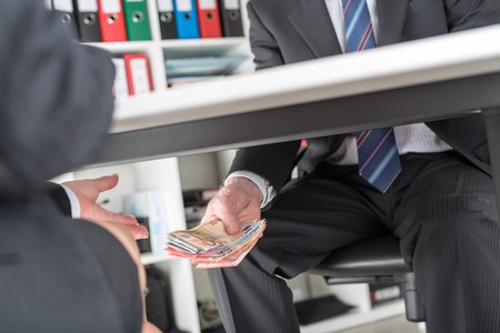 unethical: Businessman giving money under a table Stock Photo