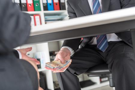 Businessman giving money under a table Banque d'images