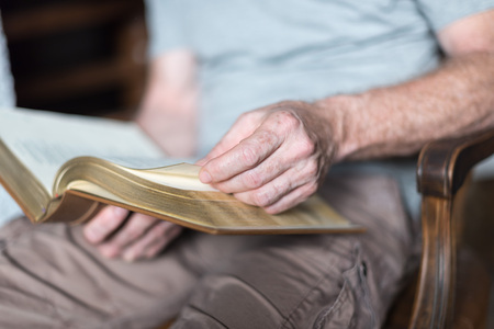 holy bible: Man sitting at home reading the Bible Stock Photo