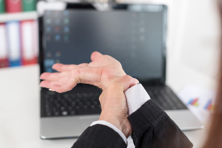 wrist pain: Businesswoman suffering from wrist pain at office Stock Photo