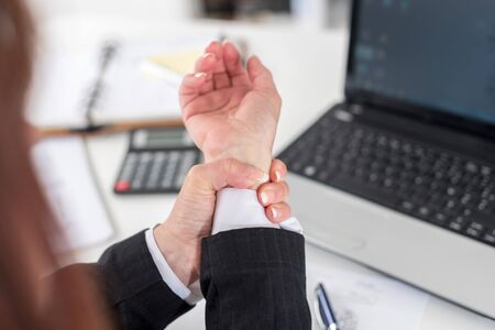 carpal tunnel syndrome: Businesswoman suffering from wrist pain at office Stock Photo