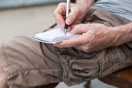 pocket book: Man sitting outdoor taking notes on a pocket book