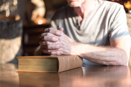 man praying: Man sitting at a table praying hands on a Bible