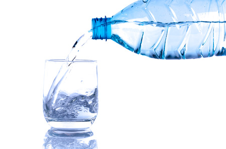 poured: Water poured from a plastic bottle into a glass, isolated on white Stock Photo